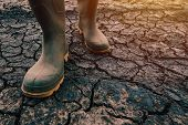 Farmer In Rubber Boots Walking On Dry Soil Ground, Global Warming And Climate Change Is Impacting Cr poster