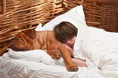 Woman and her dog comfortably sleeping in the bed