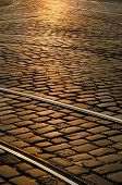 Tram rails on paved street at sunset, European old town