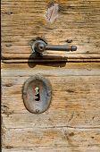 Old wooden door with rusty metal handle and key lock