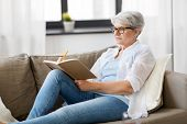 age, leisure and people concept - happy senior woman writing to notebook or diary at home poster