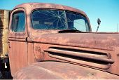 an old rusty truck sits in the blast furnice of the arizona sun in the summer reminding us of what w