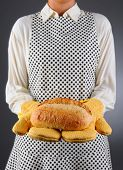 Closeup of a homemaker in an apron and oven mitts holding a fresh baked loaf of bread. Horizontal format over a light to dark background. Woman is unrecognizable. Shallow depth of field.