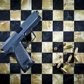 Handgun and Bullets on Checkered Chess Table