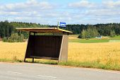 foto of bus-shelter  - Rural bus stop shelter with wheat field and village background.