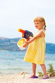 Small girl playing with water gun at the seashore