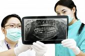 Dentist And Assistant Checking X-ray