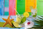 image of mojito  - Cuban Mojito cocktail in tropical colorful house on blue wood with flowers and starfish - JPG