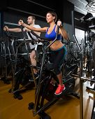 stock photo of elliptical  - elliptical walker trainer man and woman at black gym training aerobics exercise - JPG