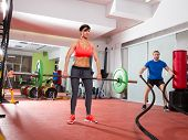 Crossfit fitness gym weight lifting bar woman and man battling ropes workout