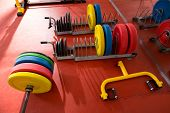 Crossfit fitness gym weight lifting bar colorful equipment on red floor
