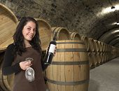 Young woman holding a wine bottle and two glasses in the cellar, surrounded by barrels