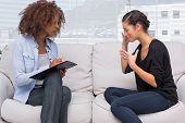 Traurige Frau im Gespräch mit ihrem Therapeuten während sie Notizen ist
