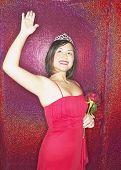 Woman wearing evening dress and tiara and waving