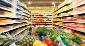 stock photo of local shop  - Full shopping cart with fruit vegetable food in supermarket - JPG