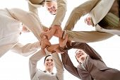 stock photo of joining hands  - Small group of business people joining hands low angle view - JPG