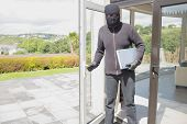 Burglar holding laptop and leaving home