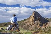 a lonely hiker sitting and contemplating mountain scenery in springtime- Eagle Nest Open Space near Fort Collins, Colorado