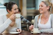 Two students having fun while sitting in college coffee shop and drinking coffee