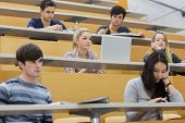 Students listening in a lecture hall in college and taking notes