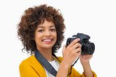 Smiling girl taking a photo and looking at camera on white background