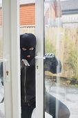 Burglar opening carefully the door with cro bar