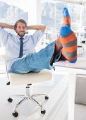 Shoeless designer kicking back at his desk and smiling