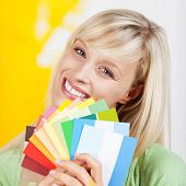 picture of interior decorator  - Gorgeous blonde woman holding up a selection of beautiful new paint colours on swatches when renovating and decorating her house - JPG