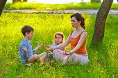 daughter mother and son sitting outdoors picnic meditation natur