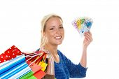 a young woman with colorful shopping bags while shopping. with euro banknotes money