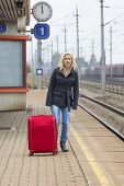 a young woman with suitcase waiting on the platform of a railway station on their train. train delay