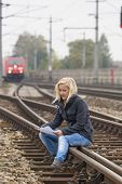 a young woman with suicide thoughts sitting on a track. holds farewell letter in his hand and thinks