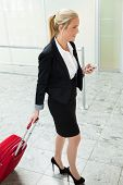 a business woman with suitcase and smartphone at an airport. mobility and communication in business