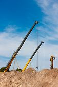 pic of auger  - Two construction cranes and one auger working at construction site peeking out from behind mounds of dirt with blue sky in background - JPG
