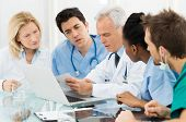 stock photo of medical exam  - Team Of Expert Doctors Examining Medical Reports at Hospital - JPG