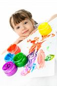 stock photo of finger-painting  - cute little girl sitting by the table and painting with finger paints - JPG