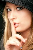 Beautiful blonde woman face showing shush with finger over mouth, looking at camera