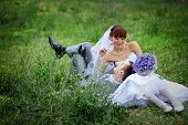 image of wedding couple  - Happy wedding couple resting on fresh green grass - JPG