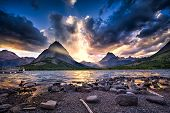 stock photo of dock a lake  - Colorful sunset over Swiftcurrent Lake in Glacier National Park Montana