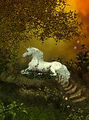 stock photo of unicorn  - A beautiful white unicorn lays underneath a forest tree to rest among the flowers - JPG