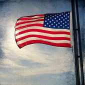 stock photo of flag pole  - The American Flag Flapping Against A Blue Sky On A Flag Pole - JPG