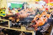 foto of spit-roast  - Meat on the spit; delicious roasted meat being prepared for eating in restaurant;