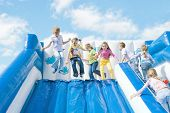 Children Jump On The Trampoline Against The Blue Sky And The Clouds