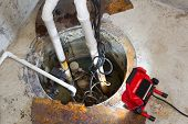 stock photo of basement  - Repairing a sump pump in a basement with a red LED light illuminating the pit and pipe work for draining ground water - JPG