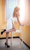 Young blonde woman wrapped in white towel looking on the window. Beautiful young woman with a towel