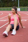 Full length of a young sporty woman sitting on the running track