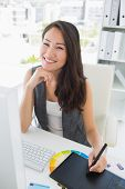 Portrait of a smiling casual female photo editor using graphics tablet in a bright office