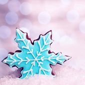 Tasty blue snowflake shaped cookie in snow decoration, traditional Christmas gingerbread, winter hol
