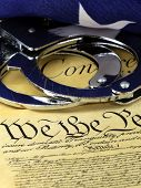 Handcuffs and flag on US Constitution - Fourth Amendment