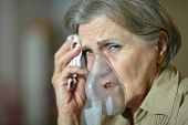 Elderly woman making inhalation